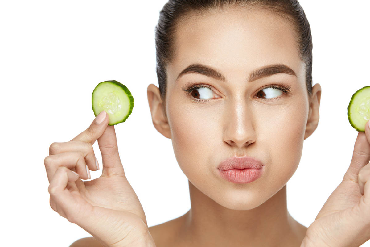 Beautiful Woman With Healthy Skin With Fresh Cucumber Slice In Hands