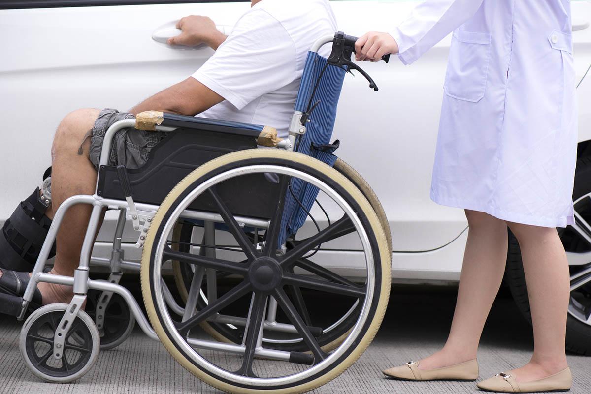 Nurse helping senior man to reach the hospital